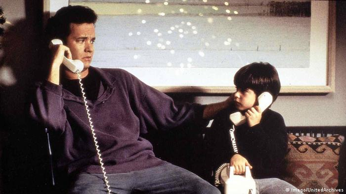 Film still from Sleepless in Seattle with Tom Hanks and little boy sitting side-by-side, both with white telephones in their hands
