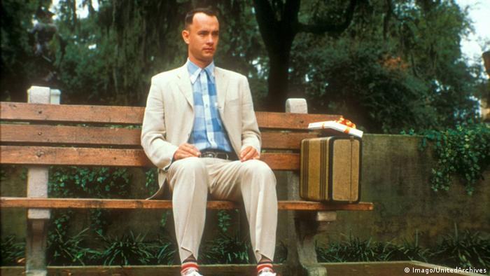 Filmstill from Forrest Gump with Tom Hanks sitting on a bench outside and a suitcase next to him