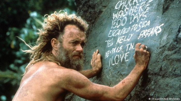 Film still from Cast Away with dirty, long-haired Tom Hanks writing on a stone with chalk