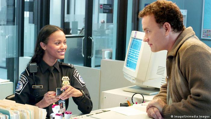 Film still from The Terminal with Tom Hanks leaning over a customs counter in an airport