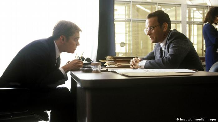 Film still from Catch Me If You Can with Leonardo DiCaprio and Tom Hanks sitting across a desk from each other