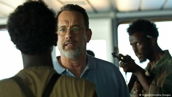 Film still from Captain Phillips with Tom Hanks, with man behind him pointing a gun at his neck