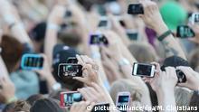 Deutschland Konzertbesucher mit Smartphones in Hamburg