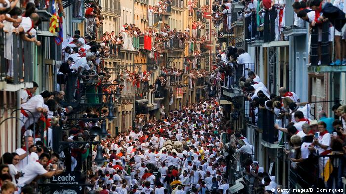 Revellers run with Fuente Ymbro's fighting bulls along Estafeta Street during the second day of the San Fermin Running of the Bulls festival on July 7, 2016 in Pamplona.