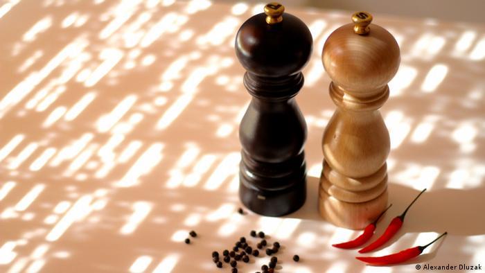 Pfeffer- und Salzmühle, davor liegen schwarze Pfefferkörner und rote Chilischoten (Foto: Alexander Dluzak).