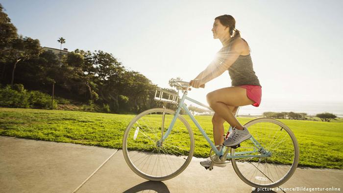 Junge Frau beim Radfahren im Park (picture alliance/Bildagentur-online)