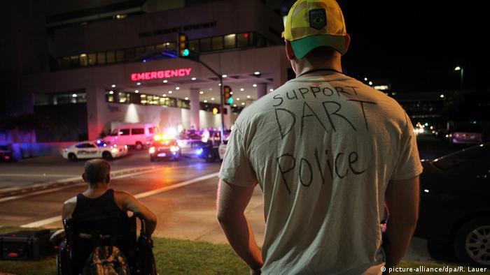 Жители Далласа смотрят на движущиеся полицейские автомобили, 8 июля