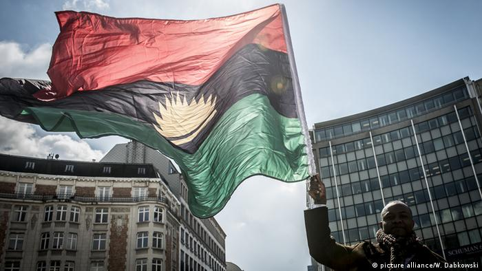 A man holds the flag which represents the defunct independence of Biafra.