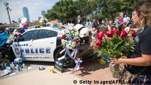08.07.2016+++ A woman places flowers at a memorial outside the Dallas Police Headquarters on July 8, 2016, following the sniper shooting during a peaceful protest the night before. The gunman who opened fire on Dallas officers during a protest against US police brutality, leaving five dead and seven others wounded, told negotiators he wanted to kill white cops, the city's police chief said July 8. +++ (C) Getty Images/AFP/L. Buckman