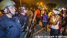 8.7.2016*** BATON ROUGE, LA -JULY 08: Protesters face off with Baton Rouge police in riot gear across the street from the police department on July 8, 2016 in Baton Rouge, Louisiana. Alton Sterling was shot by a police officer in front of the Triple S Food Mart in Baton Rouge on July 5th, leading the Department of Justice to open a civil rights investigation. (Photo by Mark Wallheiser/Getty Images) Getty Images/M. Wallheiser