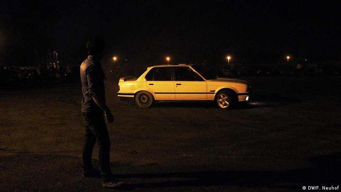 A man stands near a car at a drifting event