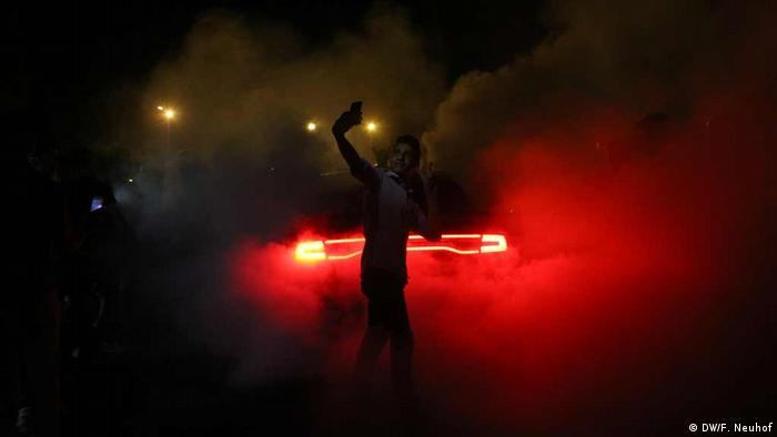 Theer Fedawi, who organizes drifting events, stands in the ring waving at a car