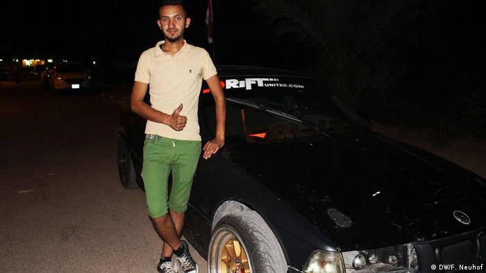 Harith Dulaimi stands next to his BMW