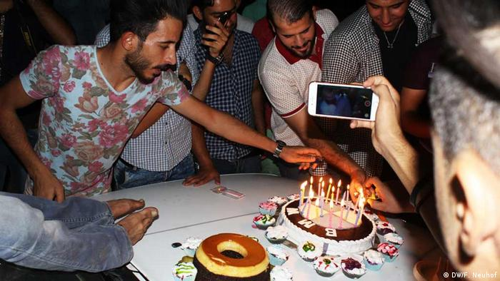 Young men light a BMW birthday cake on placed on a car hood