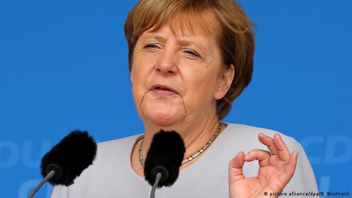 Канцлер ФРГ Ангела Меркель произносит речь перед двумя микрофонами