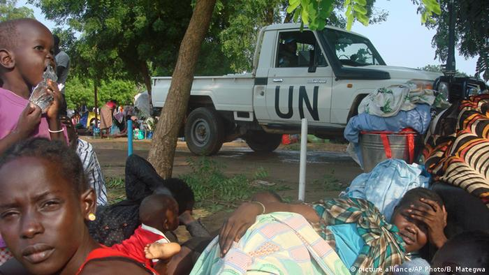Displaced persons seek refuge at a UN compound. A UN vehicle is in the background.