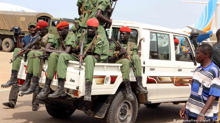Rebel soldiers with guns on a white pick-up truck.