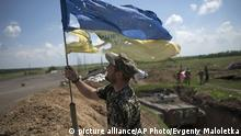 5.6.2015*** A Ukrainian soldier puts a Ukrainian flag at the Ukrainian position in Marinka, near Donetsk, eastern Ukraine, Friday, June 5, 2015. As fears persist that eastern Ukraine is about to fall back into full-scale war, a leader of the international monitoring group is urgently calling for resumed negotiations. (AP Photo/Evgeniy Maloletka)   picture alliance/AP Photo/Evgeniy Maloletka