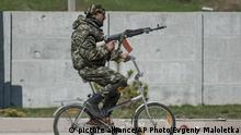 15.4.2015*** A Ukrainian serviceman rides a bicycle in Shyrokyne, eastern Ukraine, Wednesday, April 15, 2015. Russia and Ukraine agreed in Berlin on Monday to call for the pullback of smaller-caliber weapons from the front lines of the conflict that has claimed more than 6,000 lives. (AP Photo/Evgeniy Maloletka)   picture alliance/AP Photo/Evgeniy Maloletka