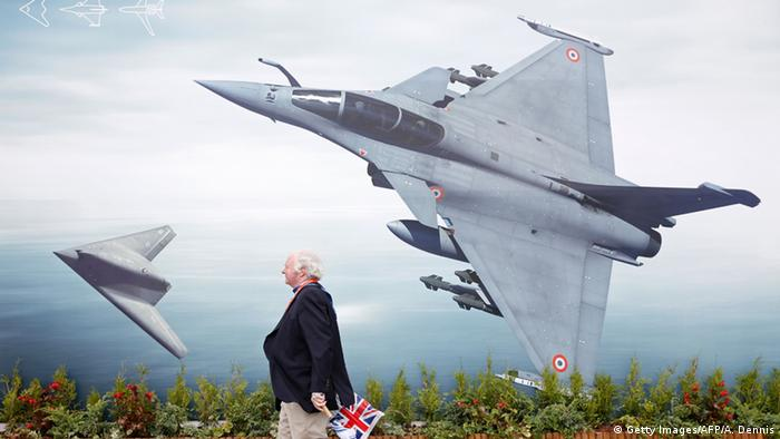 Farnborough air show visitor walking past poster of fighter jets