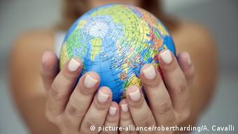 Frau hält Weltkugel in Händen
