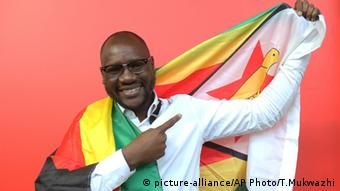 Evans Mawarire smiles as he poses with a Zimbabwean flag (picture-alliance/AP Photo/T.Mukwazhi)