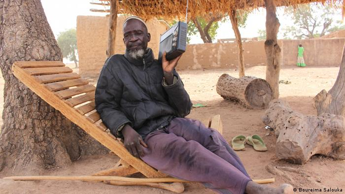 Seydou Ilboudo sits in a wooden chair and listens to the radio