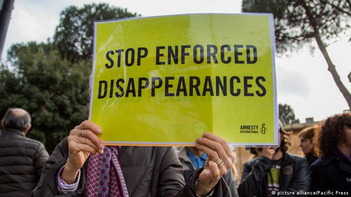 A protester holds up a sign saying Stop Enforced Disappearances (picture alliance/Pacific Press)