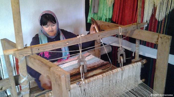 Женщина ткет ковер на старинном станке