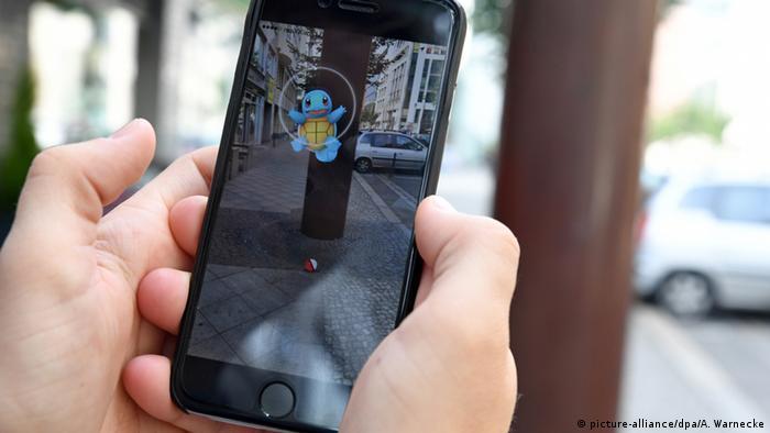 Deutschland Mann spielt Pokemon Go auf Smartphone