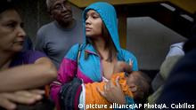 3.5.2016*** In this Tuesday, May 3, 2016 photo, Madeley Vasquez, 16, breast feeds her one-year-old son Joangel as she waits in line outside a supermarket to buy food in Caracas, Venezuela. Vasquez once ran down the block to avoid getting caught up in a knife fight that broke out when a woman was accused of cutting the line. (AP Photo/Ariana Cubillos) | picture alliance/AP Photo/A. Cubillos