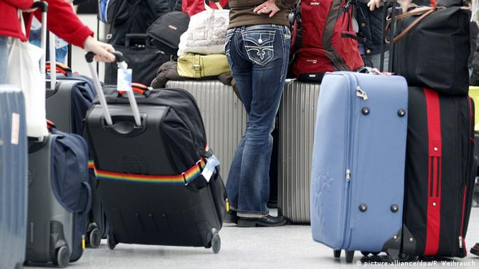 Passengers with suitcases waiting at Dusseldorf airport, Copyright picture-alliance/dpa/R. Weihrauch