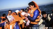 A man holding a newborn baby gets off a dinghy as refugees and migrants riding a dinghy reach the shores of the Greek island of Lesbos after crossing the Aegean Sea from Turkey on November 12, 2015. EU leaders attending a summit with their African counterparts approved a 1.8-billion-euro trust fund for Africa aimed at tackling the root causes of mass migration to Europe. +++ (C) Getty Images/AFP/B. Kilic