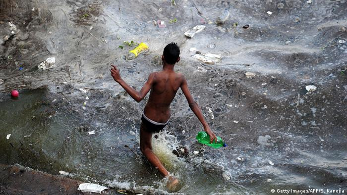 A boy walks into the polluted waters of the river