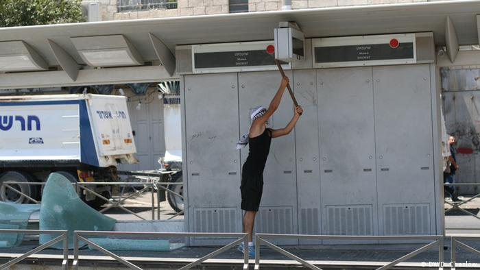 A Palestinian protester hacks apart Shuafat train station on July 14, 2014 in response to the murder of Mohammed Abu Khdeir