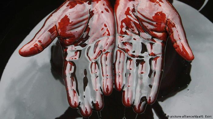 A pair of hands coated in oil