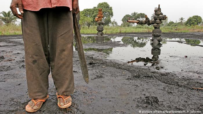 Farmer Bakpa Birabil stands in front of two leaking oil wells on his farm in Ogoniland, which has been owned by his family for centuries.
