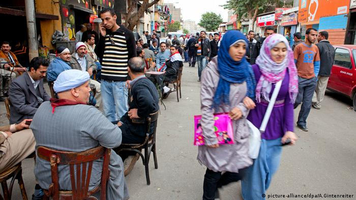 Young women walk past a line of men sitting outside a café near Tahrir Square in Cairo