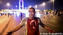 A man covered with blood stands near the Bosphorus bridge as Turkish military clash with people at the entrance to the bridge in Istanbul on July 16, 2016. Turkish military forces on July 16 opened fire on crowds gathered in Istanbul following a coup attempt, causing casualties, an AFP photographer said. The soldiers opened fire on grounds around the first bridge across the Bosphorus dividing Europe and Asia, said the photographer, who saw wounded people being taken to ambulances. / AFP / Bulent KILIC (Photo credit should read BULENT KILIC/AFP/Getty Images) Getty Images/B.Kilic Getty Images/B.Kilic/G.Ozturk