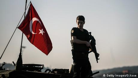 Türkei Polizist auf einem Panzer neben türkischer Flagge
