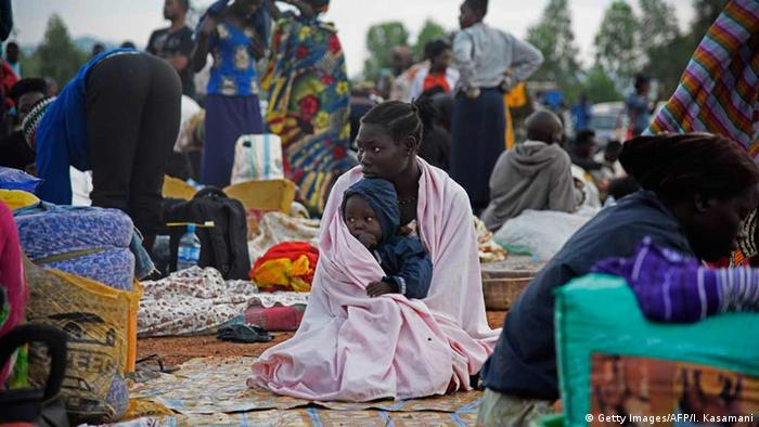 A woman carries a child on her knees as she sits inside a make-shift camp at Nimule border, in Amuru Distric in Uganda