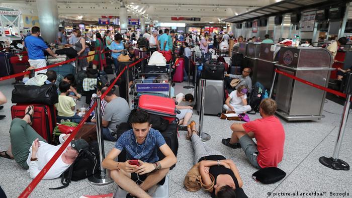 Passagiere warten in einem überfüllten Flughafen