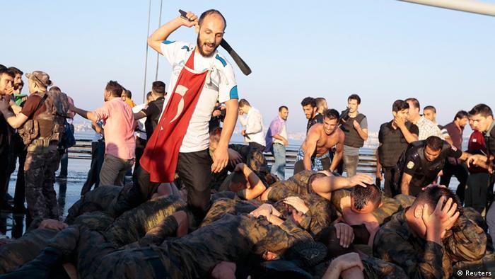 Человек бьет дубинкой солдат, принимавших участие в мятеже