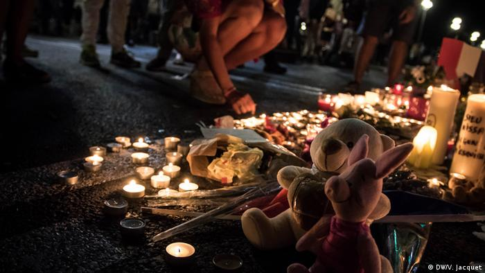 candles, stuffed animals, person kneeling