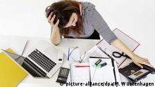 Eine Frau sitzt überfordert an ihrem Schreibtisch