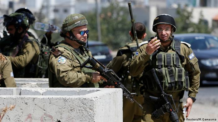 Israeli soldiers gather at scene of a stabbing attack near the Arroub refugee camp in the West Bank.