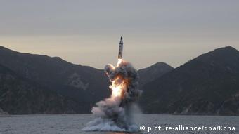 A North Korean ballistic missile rises out of the water.