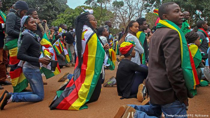 Young protesters in Harare kneel for prayer(Getty Images/AFP/J. Njikizana)