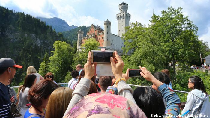 Tourists taking pictures of Neuschwanstein, Copyright: picture-alliance/dpa/K. J. Hildenbrand