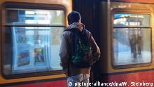 Ein junger Migrant mit einem Rucksack steht auf einem S-Bahn-Gleis in Berlin an der S-Bahnstation Schöneberg am 03.02.2016. Eine S-Bahn fährt dabei durch den Bahnhof. +++(c) picture-alliance/dpa/W. Steinberg